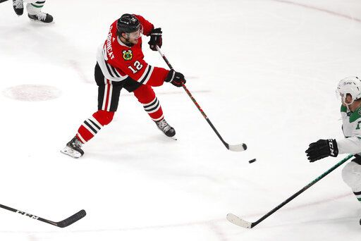 Chicago Blackhawks left wing Alex DeBrincat (12) shoots the puck for a goal against the Dallas Stars during the second period of an NHL hockey game Tuesday, April 6, 2021, in Chicago.