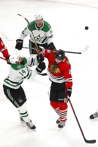 Dallas Stars left wing Jamie Benn (14) and Chicago Blackhawks center Ryan Carpenter (22) battle for the puck during the second period of an NHL hockey game Tuesday, April 6, 2021, in Chicago.