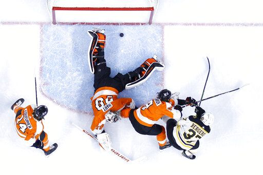 Boston Bruins' Patrice Bergeron, right, scores a goal past Philadelphia Flyers goaltender Carter Hart (79) as Ivan Provorov (9) and Sean Couturier (14) defend during the first period of an NHL hockey game, Tuesday, April 6, 2021, in Philadelphia.