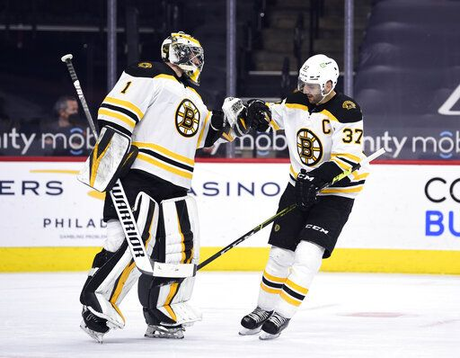 Boston Bruins' Patrice Bergeron, right, high-fives Jeremy Swayman after Bergeron scored a goal during the first period of an NHL hockey game against the Philadelphia Flyers, Tuesday, April 6, 2021, in Philadelphia.