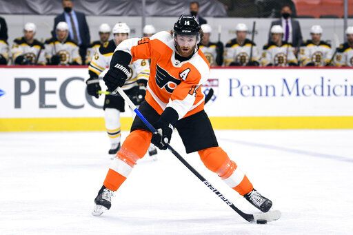 Philadelphia Flyers' Sean Couturier passes the puck during the first period of an NHL hockey game against the Boston Bruins, Tuesday, April 6, 2021, in Philadelphia.