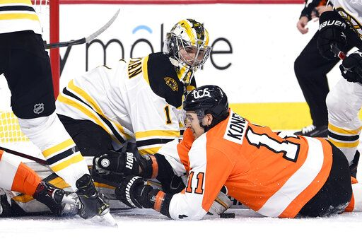 Boston Bruins goaltender Jeremy Swayman, left, makes a save as Philadelphia Flyers' Travis Konecny (11) looks for the rebound during the first period of an NHL hockey game, Tuesday, April 6, 2021, in Philadelphia.