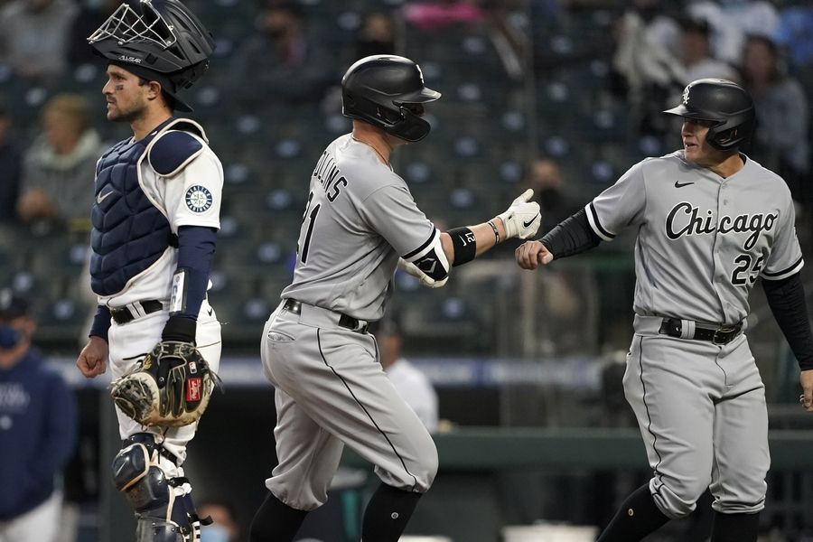 Chicago White Sox's Zack Collins, center, is greeted by Andrew Vaughn, right, as Seattle Mariners catcher Luis Torrens stands nearby after Collins hit a three-run home run during the second inning of a baseball game Tuesday, April 6, 2021, in Seattle.