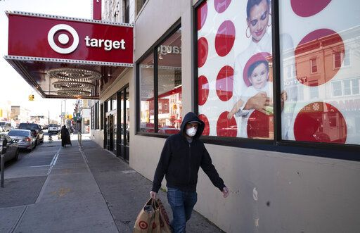 FILE - In this April 6, 2020 file photo, a customer wearing a mask carries his purchases as he leaves a Target store during the coronavirus pandemic, in the Brooklyn borough of New York. Target says it will spend a a total of more than $2 billion at Black-owned businesses by 2025 as part of its effort to advance racial equity. As part of its program, the Minneapolis-based discounter will add products from more than 500 Black-owned businesses across all types of merchandising areas.