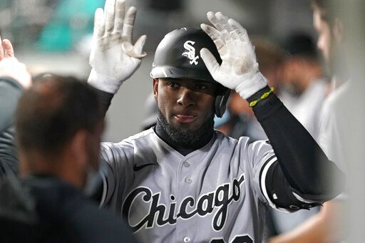 Chicago White Sox's Luis Robert is greeted in the dugout after he hit a two-run home run during the fifth inning of the team's baseball game against the Seattle Mariners, Tuesday, April 6, 2021, in Seattle.