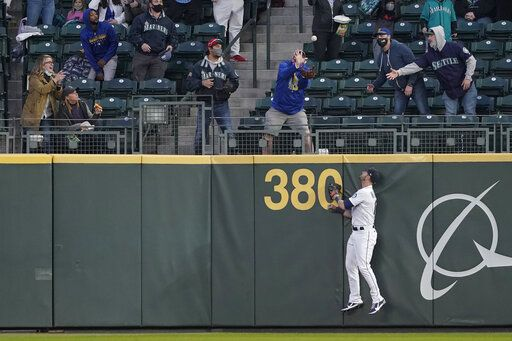 Seattle Mariners right fielder Mitch Haniger watches as a fan catches a three-run home run hit by Chicago White Sox's Zack Collin during the second inning of a baseball game Tuesday, April 6, 2021, in Seattle.