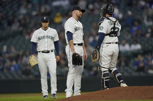 Seattle Mariners starting pitcher James Paxton, center, waits near the mound with catcher Luis Torrens after Paxton suffered an injury during the second inning of the team's baseball game against the Chicago White Sox, Tuesday, April 6, 2021, in Seattle. Paxton left the game and was replaced by Nick Margevicius.