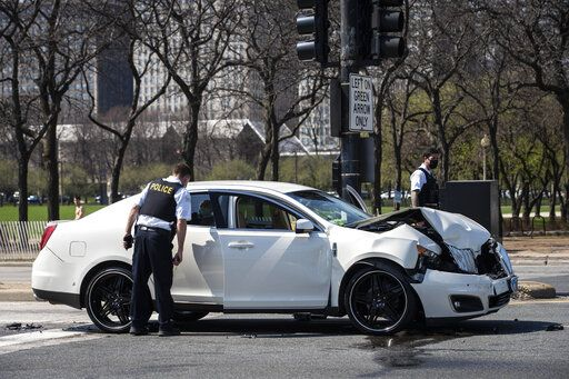 Chicago police investigate in the northbound lanes of Lake Shore Drive at East Monroe Street, where a 2-year-old boy was shot in the head while he was traveling inside a car near Grant Park, Tuesday, April 6, 2021. (Ashlee Rezin Garcia/Chicago Sun-Times via AP)