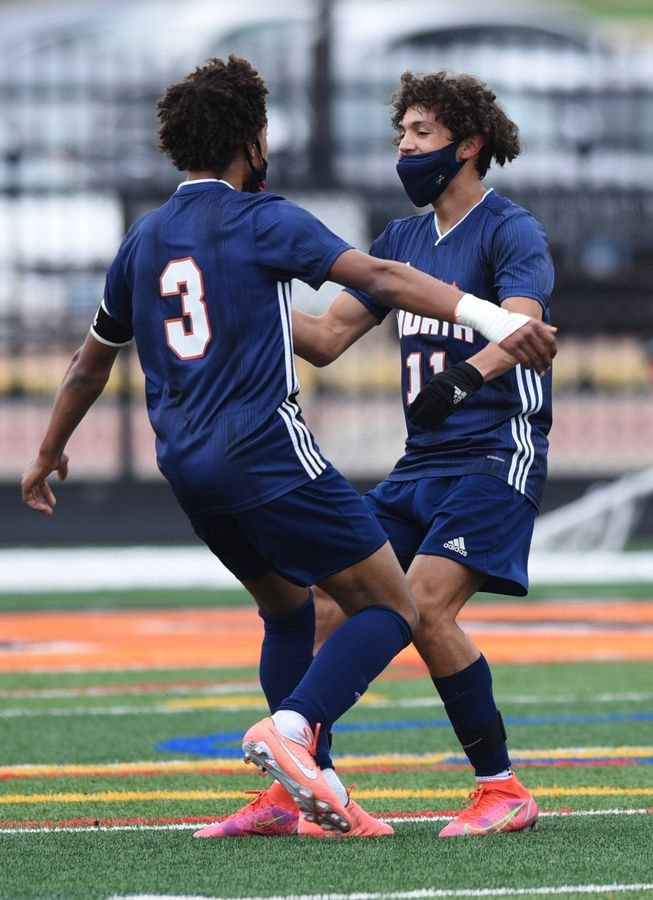 Naperville North's Alex Barger, right, celebrates his goal with teammate Tyson Amoo-Mensah during the first half of Saturday's game against St. Charles East.