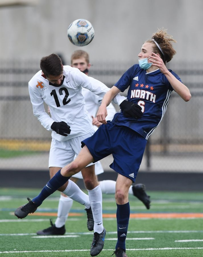 St. Charles East's Elia Desario, left, directs the ball past Naperville North's Cam Radeke with a header during Saturday's game in Naperville.