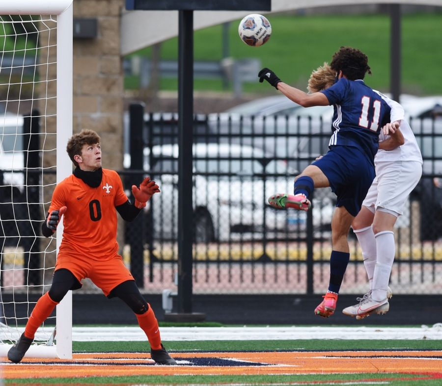 Naperville North's Alex Barger (11) scores on a header against St. Charles East goalkeeper Jake Boecher, left, during the first half of Saturday's game in Naperville.