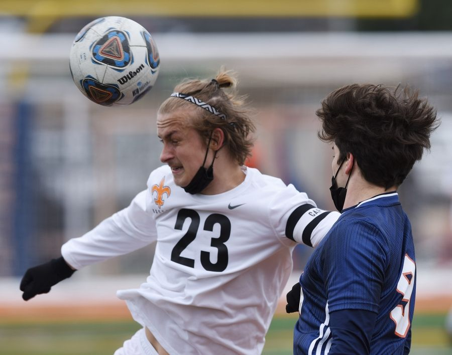 St. Charles East's Jake Maslowski, left, directs the ball with a header in front of Naperville North's Keegan Flaherty during Saturday's game in Naperville.