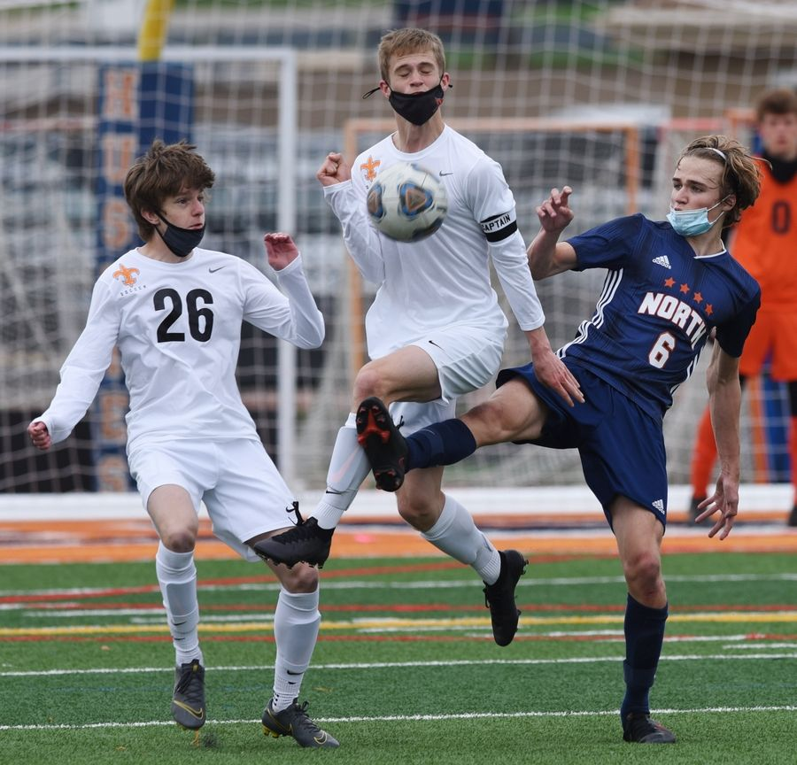 St. Charles East's Aaron Frost, left, and Ryan Champine try to control the ball while working against Naperville North's Cam Radeke during Saturday's game in Naperville.