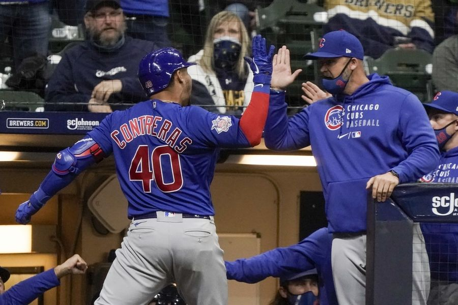 Chicago Cubs' Willson Contreras celebrates with manager David Ross after hitting a two-run home run during the eighth inning of a baseball game against the Milwaukee Brewers Tuesday, April 13, 2021, in Milwaukee.