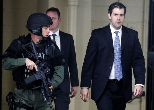 FILE- In this Dec. 5, 2016 file photo, Michael Slager, at right, walks from the Charleston County Courthouse under the protection from the Charleston County Sheriff's Department after a mistrial was declared for his trial in Charleston, S.C. Slager, a former South Carolina police officer serving 20 years in prison for killing an unarmed Black man who was running away from a traffic stop, said his lawyer never told him about a plea offer from prosecutors that could have cut years off his sentence. He is requesting a new sentence in federal court this week.