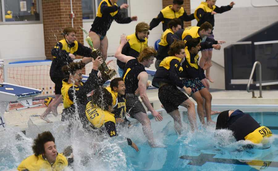 The Glenbrook South High School boys swim team jumps into the pool with the Illinois Swimming and Diving Association state championship trophy Friday. The team was recognized during halftime at South's football game against Maine South.
