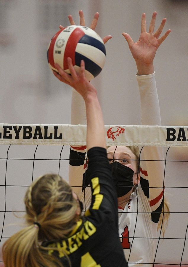 Barrington's Jenna Meitzler blocks a shot by Fremd's Samantha Gump in a girls volleyball match in Barrington Wednesday, April 14, 2021.