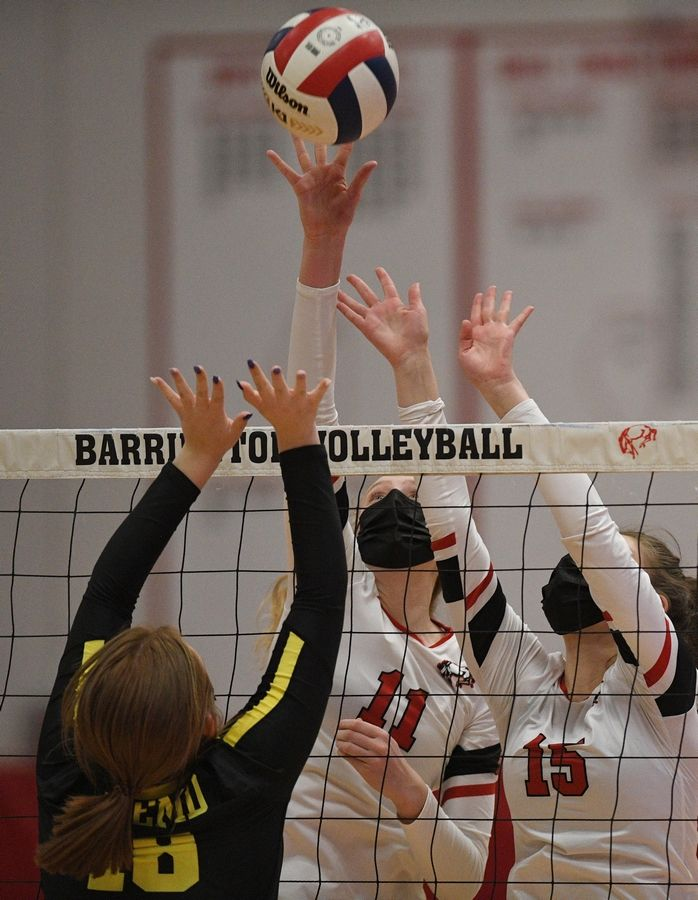 Barrington's Jenna Meitzler and Christina Copertino meet Fremd's Allie Belmonte at the net in a girls volleyball match in Barrington Wednesday, April 14, 2021.