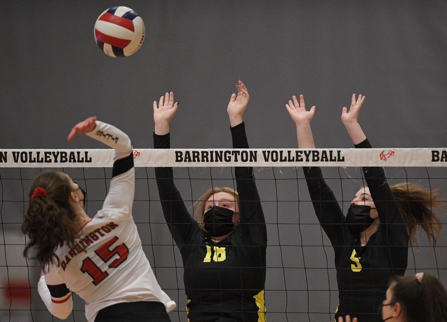 Fremd's Allie Belmonte and Sarah Graham defend a shot by Barrington's Christina Copertino in a girls volleyball match in Barrington Wednesday, April 14, 2021.