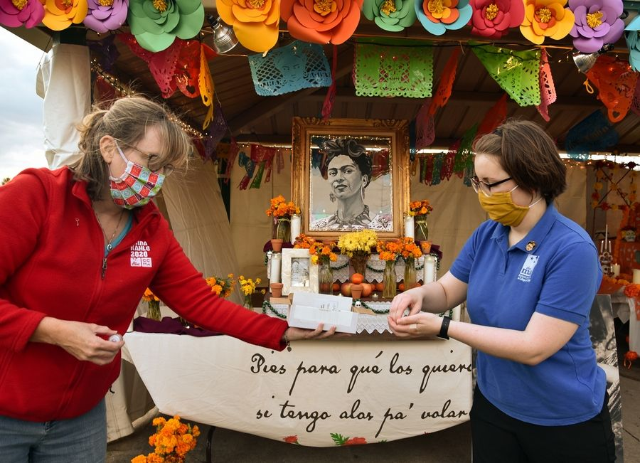 "Janey Sarther, left, of the McAninch Arts Center and Molly Junokas, project coordinator for the ""Frida Kahlo: Timeless"" exhibit at the College of DuPage, set up a display during the ""Día de los Muertos"" celebration last fall at Camera Park in Glendale Heights. The drive-by event, hosted by the Cleve Carney Museum of Art and MAC, collected more than 100 bags and 10 cases of nonperishable food items, diapers, baby wipes and first aid supplies."