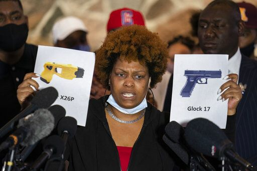 Naisha Wright, aunt of the deceased Daunte Wright, holds up images depicting X26P Taser and a Glock 17 handgun during a news conference at New Salem Missionary Baptist Church, Thursday, April 15, 2021, in Minneapolis.