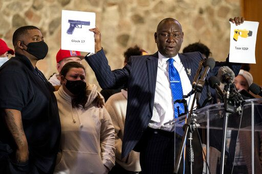 Attorney Ben Crump, representing the family of Daunte Wright, holds up images depicting X26P Taser and a Glock 17 handgun during a news conference at New Salem Missionary Baptist Church, Thursday, April 15, 2021, in Minneapolis.