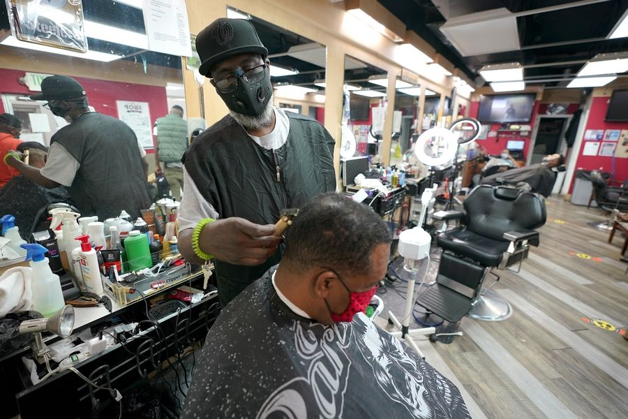 Wallace Wilson, top, cuts the hair of James McRae in Hyattsville, Md. Wilson is a member of the Health Advocates In Reach & Research (HAIR) program, which helps barbers and hair stylists to get certified to talk to community members about health.