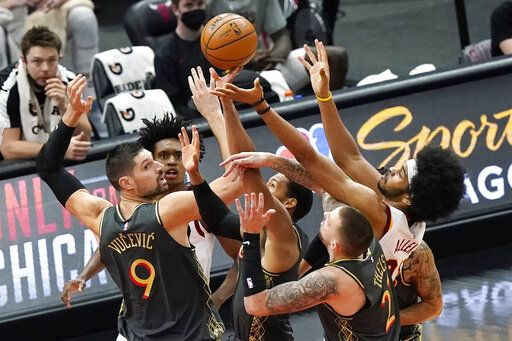Chicago Bulls center Nikola Vucevic (9), forward Garrett Temple and center Daniel Theis (27) and Cleveland Cavaliers guard Collin Sexton, left, rear, and center Jarrett Allen (31) vie for a rebound during the first half of an NBA basketball game in Chicago, Saturday, April 17, 2021.