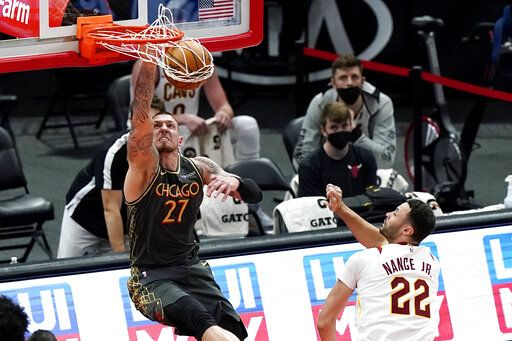 Chicago Bulls center Daniel Theis dunks as Cleveland Cavaliers forward Larry Nance Jr. watches during the second half of an NBA basketball game in Chicago, Saturday, April 17, 2021.