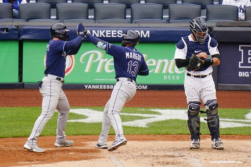 New York Yankees catcher Gary Sanchez, right, reacts as Tampa Bay Rays' Manuel Margot, center, celebrates with Austin Meadows after they scored on a two-run home run by Margot during the fourth inning of a baseball game Saturday, April 17, 2021, in New York.