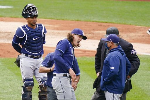 Tampa Bay Rays starting pitcher Tyler Glasnow reacts to pain as a trainer helps him during the fifth inning of a baseball game against the New York Yankees as catcher Francisco Mejia, left, watches Saturday, April 17, 2021, in New York.