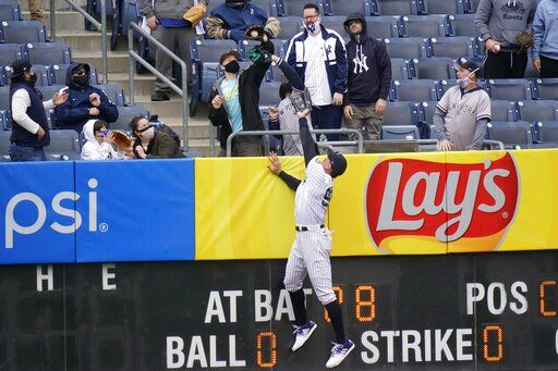 A fan catches a ball hit by Tampa Bay Rays' Francisco Mejia for a home run as New York Yankees right fielder Aaron Judge (99) leaps at the wall during the second inning of a baseball game Saturday, April 17, 2021, in New York.