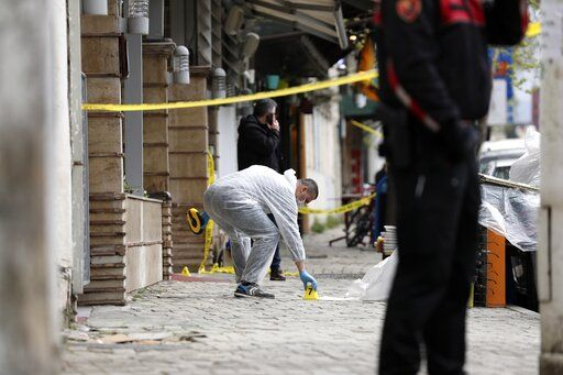 A policeman investigates the area outside Dine Hoxha mosque after a knife attack in Tirana, Albania, Monday, April 19, 2021.  Monday, April 19, 2021. Police say an Albanian man with a knife has attacked five people at a mosque in the capital of Tirana. A police statement said Rudolf Nikolli, 34, entered the Dine Hoxha mosque in downtown Tirana about 2:30 p.m. and wounded five people with a knife.