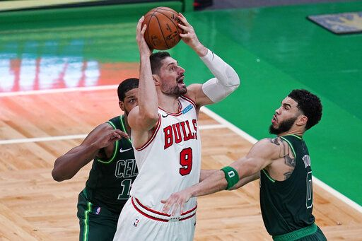 Chicago Bulls center Nikola Vucevic (9) shoots while pressured Boston Celtics forward Jayson Tatum, right, and center Tristan Thompson, rear, during the second half of an NBA basketball game, Monday, April 19, 2021, in Boston.