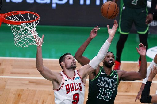 Chicago Bulls center Nikola Vucevic (9) reaches for a rebound against Boston Celtics center Tristan Thompson (13) during the second half of an NBA basketball game, Monday, April 19, 2021, in Boston.