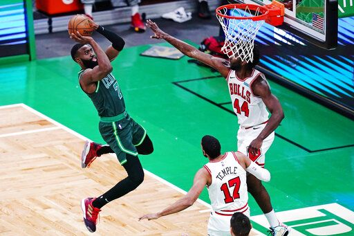 Boston Celtics guard Jaylen Brown (7) takes a shot against Chicago Bulls forward Patrick Williams (44) and forward Garrett Temple (17) during the first half of an NBA basketball game, Monday, April 19, 2021, in Boston.