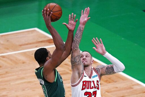 Chicago Bulls center Daniel Theis, right,  tries to block Boston Celtics center Tristan Thompson, left, during the first half of an NBA basketball game, Monday, April 19, 2021, in Boston.