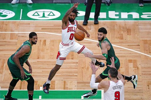 Chicago Bulls guard Coby White, center, passes the ball to Nikola Vucevic (9) while pressured by Boston Celtics forward Jayson Tatum, right, and center Tristan Thompson, left, during the first half of an NBA basketball game, Monday, April 19, 2021, in Boston.