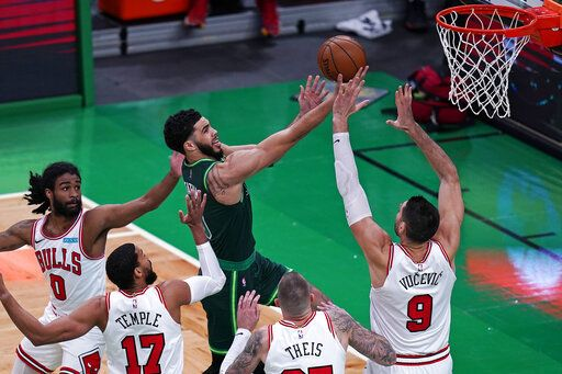Boston Celtics forward Jayson Tatum, center, drives to the basket against the Chicago Bulls defense during the first half of an NBA basketball game, Monday, April 19, 2021, in Boston.