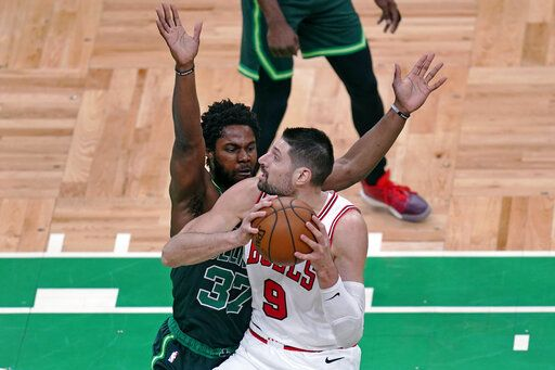 Chicago Bulls center Nikola Vucevic, right, drives to the basket against Boston Celtics forward Semi Ojeleye, left, during the first half of an NBA basketball game, Monday, April 19, 2021, in Boston.