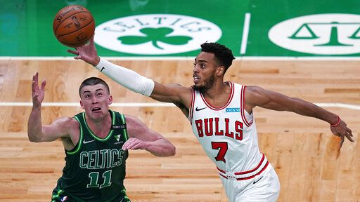 Chicago Bulls forward Troy Brown Jr., left, grabs a rebound over Boston Celtics guard Payton Pritchard, right,  during the first half of an NBA basketball game, Monday, April 19, 2021, in Boston.