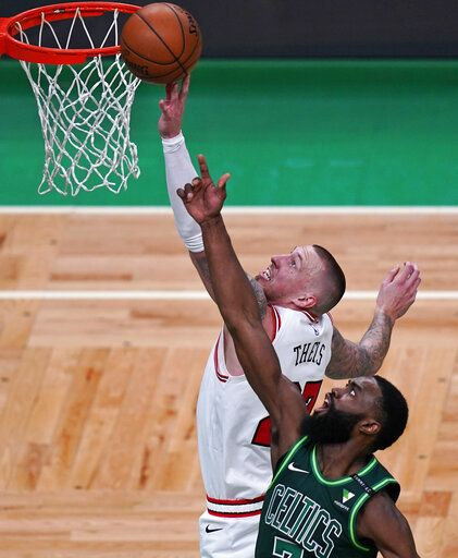 Chicago Bulls center Daniel Theis, left, tries to tip in a rebound against Boston Celtics guard Jaylen Brown, right, during the first half of an NBA basketball game, Monday, April 19, 2021, in Boston.