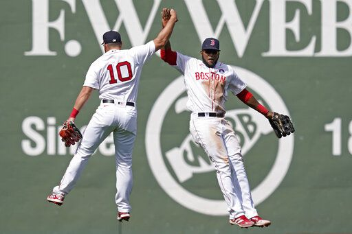 Boston Red Sox outfielders Hunter Renfroe (10) and Franchy Cordero, right, celebrate their 11-4 victory over the Chicago White Sox after a baseball game at Fenway Park, Monday, April 19, 2021, in Boston.