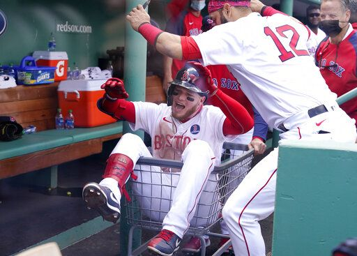 Boston Red Sox's Alex Verdugo is pushed through the dugout in a basket as he celebrates his solo home run with teammate Marwin Gonzalez (12) in the third inning of a baseball game against the Chicago White Sox at Fenway Park, Monday, April 19, 2021, in Boston.