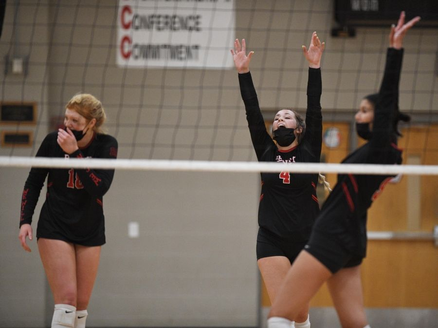 Benet Academy's Rachel Muisenga, left, Kyla Kenney and Katherine Mojica, right, celebrate a point against Marist in the East Suburban Catholic Conference girls volleyball tournament championship match Wednesday, April 21, 2021.