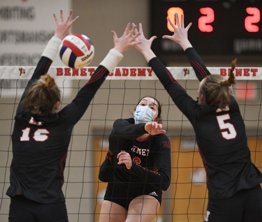 Benet Academy's Ann Marie Remmes sends a shot past Marist's Ewelina Gacek and Mary Clare Brusek in the East Suburban Catholic Conference girls volleyball tournament championship match Wednesday, April 21, 2021.