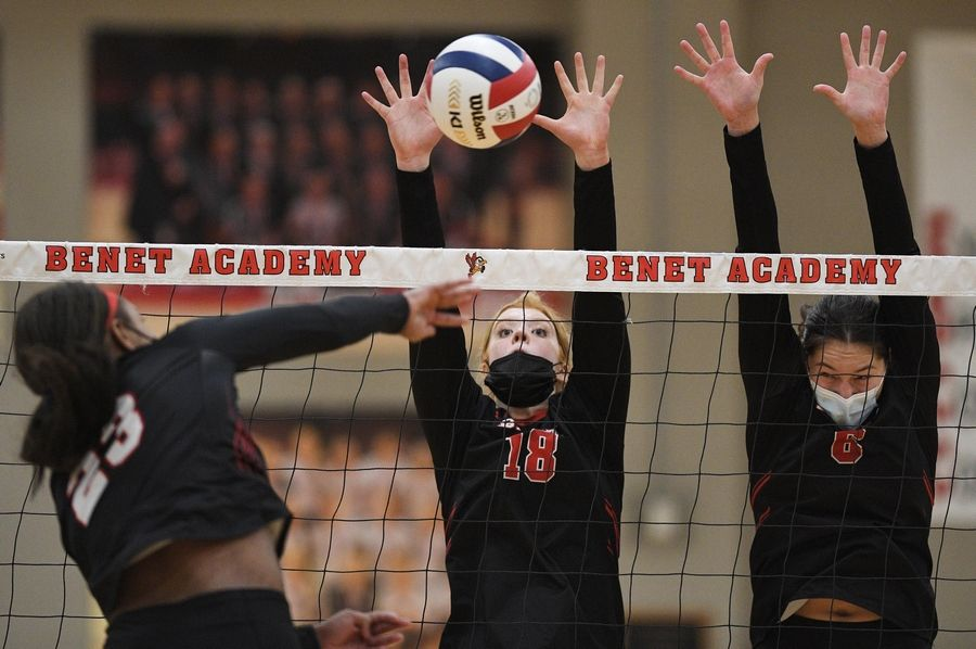 Benet Academy's Rachel Muisenga and Ann Marie Remmes try to block a shot from Marist's Kamryn Chaney in the East Suburban Catholic Conference girls volleyball tournament championship match Wednesday, April 21, 2021.