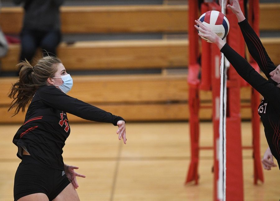 Benet Academy's Olivia Gonnella hits against Marist's Mary Clare Brusek in the East Suburban Catholic Conference girls volleyball tournament championship match Wednesday, April 21, 2021.