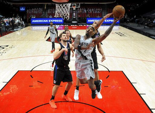 Portland Trail Blazers forward Rondae Hollis-Jefferson, right, drives to the basket on Los Angeles Clippers center Ivica Zubac, left, during the first half of an NBA basketball game in Portland, Ore., Tuesday, April 20, 2021.