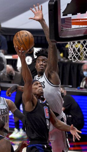 Portland Trail Blazers forward Nassir Little, right, blocks the shot of Los Angeles Clippers guard Rajon Rondo, left, during the first half of an NBA basketball game in Portland, Ore., Tuesday, April 20, 2021.